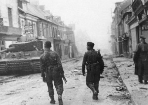 Two Leibstandarte Panzergrenadiers on the Rue Pasteur walk past Wittmann's disabled Tiger outside the Huet-Godefroy store