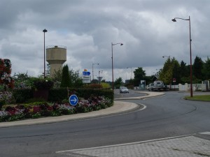 The Tilly Junction/D 675 towards Caen in 2014. Note the distinctive water tower on the left